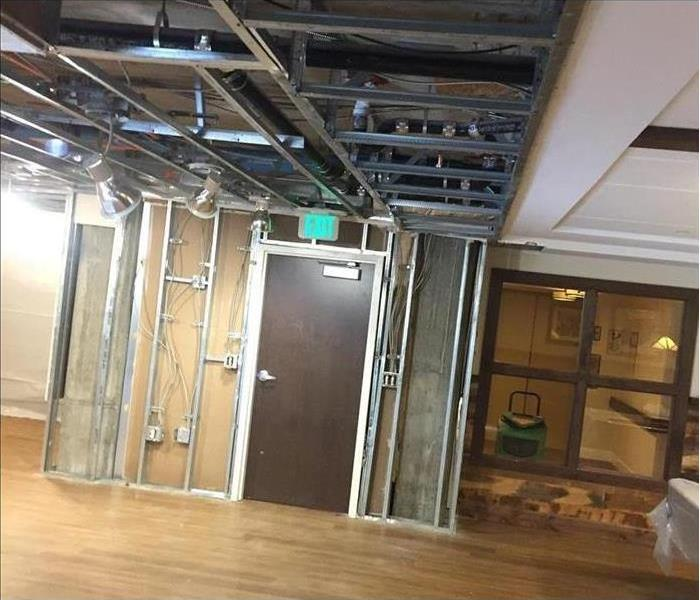 Same commercial space w/ drywall and ceiling panels removed and dry floor