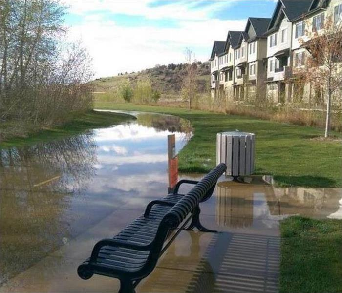 Deep flooding on apartment complex sidewalk next to river