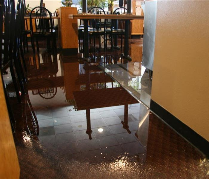 interior dining room of a restaurant with an inch of water on the carpeted floor